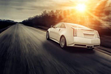 Car drive speed fast on the road at sunset cadillac