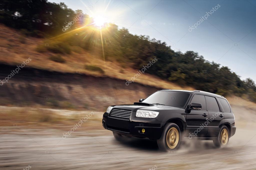 Car drive speed fast on the dust off-road subaru forester at