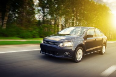 Fast drive car speed on the road at summertime sunset volkswagen polo sedan