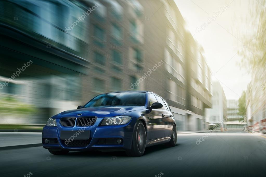 Fast drive blue bmw car speed on the road in the city