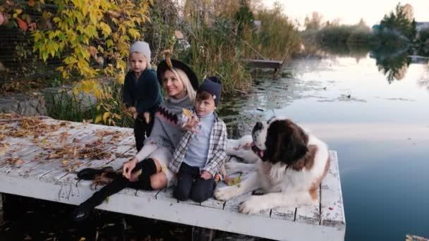 Šťastná velká rodina se svým psem na procházce při západu slunce v blízkosti jezera na podzim