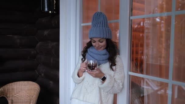 Vonzó fiatal nő fehér ruhában, közelről egy csésze teát tart a kezében az erkélyen. Boldog, mosolygós és nyugodt..