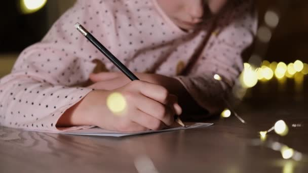 Christmas moment. A charming little girl is writing a letter to Santa Claus. Hands close up