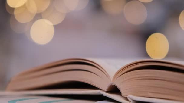 Egy nyitott könyv fekszik egy ajándék doboz hátterében fények
