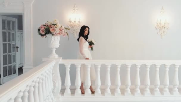 Gyönyörű fiatal menyasszony esküvői ruhában, csokorral a kezében sétál.