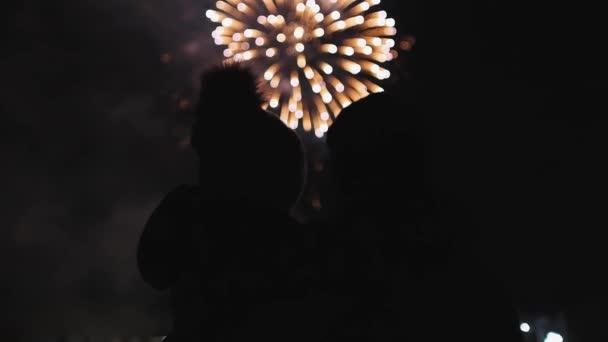 Holčička v klobouku s pamponem v rukou svých otců, dívající se na ohňostroj, ohňostroj na prázdninách