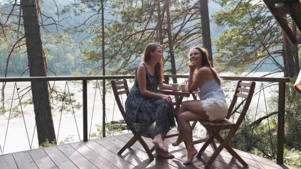 Dvě atraktivní dívky sedět u konferenčního stolku na balkóně, vychutnat si přírodu v horách.