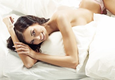 Laughing half-naked woman in the bedroom