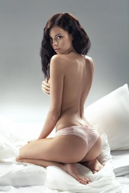 Delicate brunette woman posing in bedroom