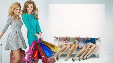 Group of cheerful girlfriends advertising shopping sales