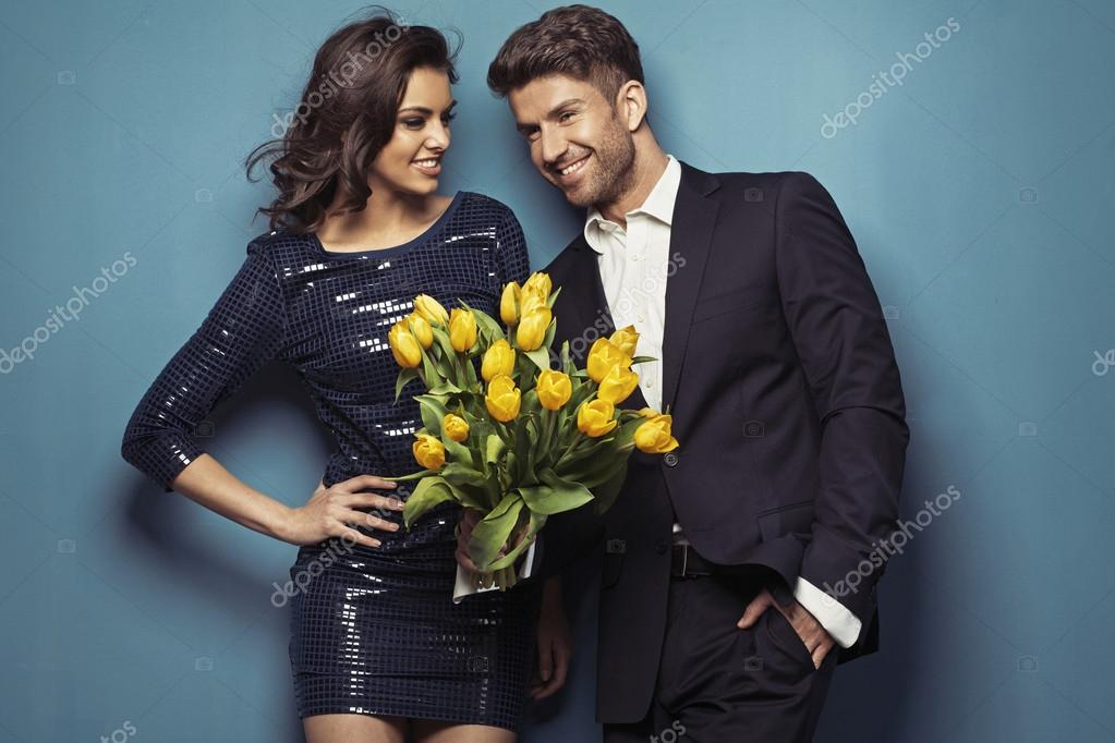 Cheerful couple posing with tulips