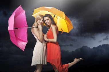 Two cheerful young ladies posing in the rain