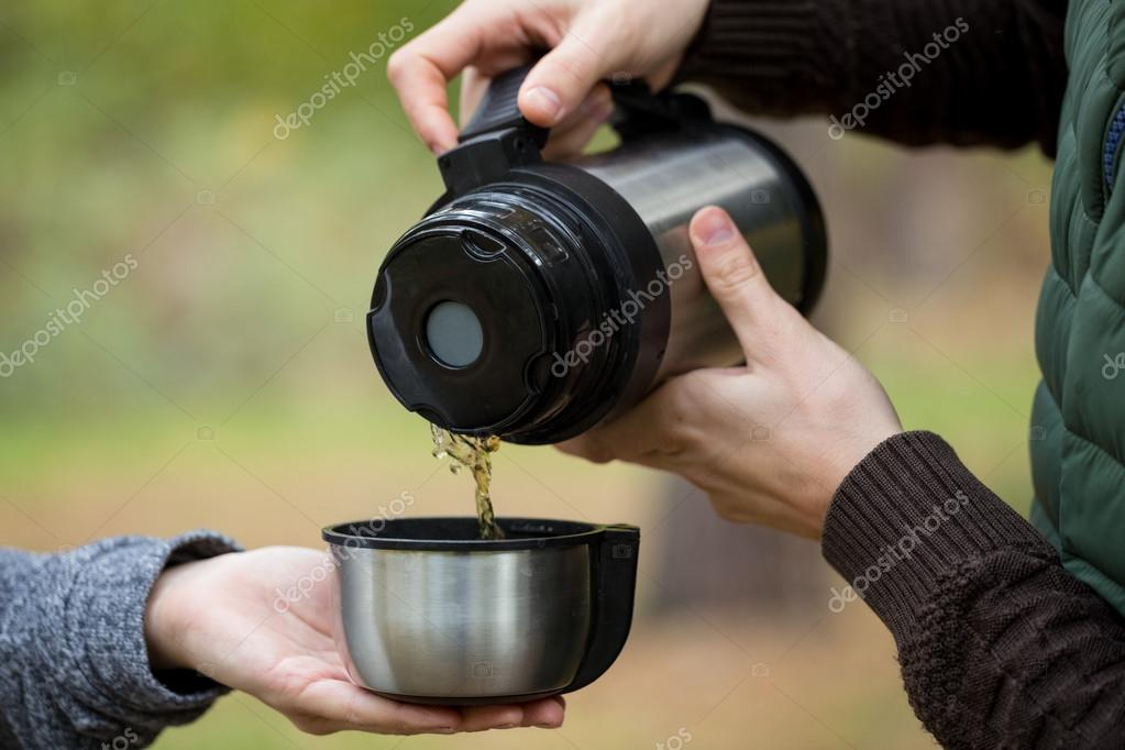 Man pours tea from the thermos his girlfriend.