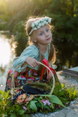 Russian girl in folk costume is walking on a summer evening in the woods with a basket