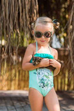 girl in a bathing suit and sunglasses holding his little kitten and looking at him with love