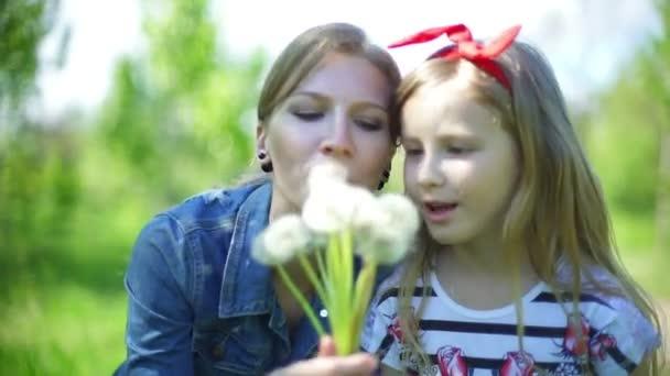 Kleines Mädchen mit Mutter sitzen auf der Wiese weht Löwenzahn
