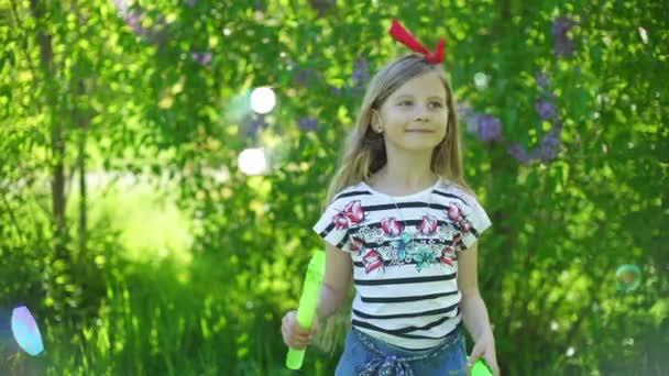 Bambino felice che soffia bolle di sapone nel parco primavera