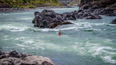 Kayakers navigating through the White Water Rapids and around Rocks