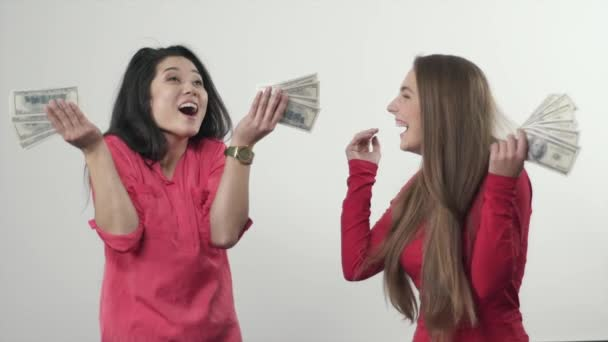 Two girls standing in the rain from money that falling from the sky. Slow Motion