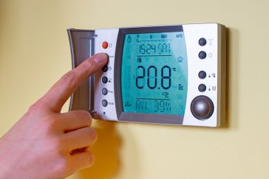 Closeup of a woman's hand setting the room temperature on a mode