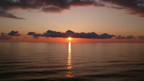 Vörös naplemente a tenger felett videó A nap megérinti a horizontot. Vörös ég, sárga nap és csodálatos tenger. Nyári naplemente. A nap az orsós felhőkben Fantasztikus természetes naplementék