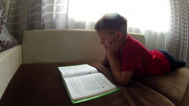 Vicces kisfiú feküdt a kanapén, és lapozható könyv