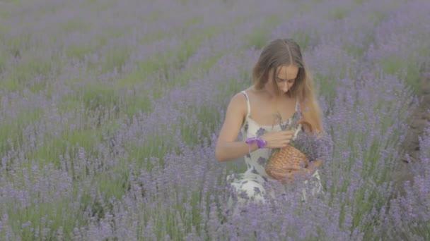 Šťastný a pohodovou dívku sedící uprostřed pole kvetoucí levandule