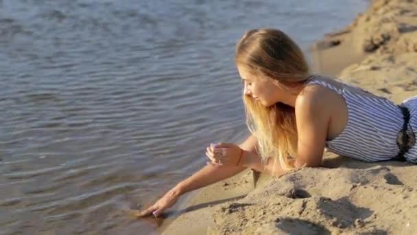 dívka, spočívající na písku poblíž řeky večer