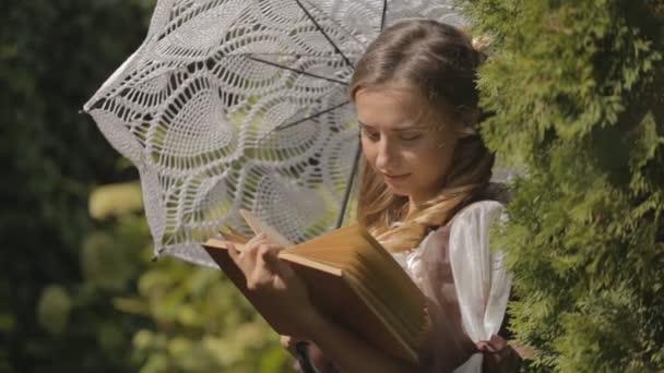 girl reading a book while standing under an umbrella.