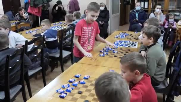 GOMEL, BELARUS - December 27, 2020: Festive New Years checkers tournament among children. Simultaneous game with champions for candy