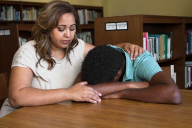 Teacher consoling a teenage student.