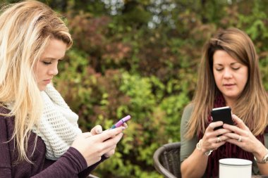 Mother and teenage daughter not spending time together and text messaging.
