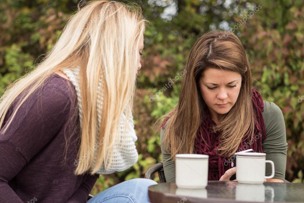 Woman checking her messages while hanging out with a friend.