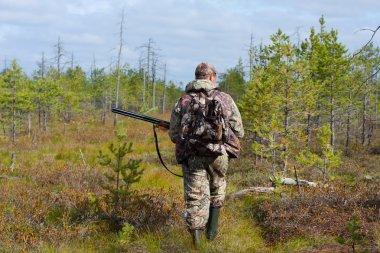 Hunter walking on the swamp