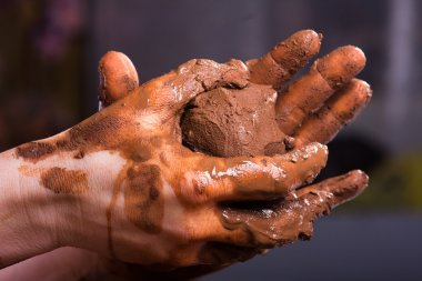 closeup of hands of a potter with clay