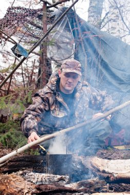 hunter prepares food on fire