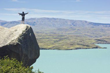man on the cliff in mountains at above lake