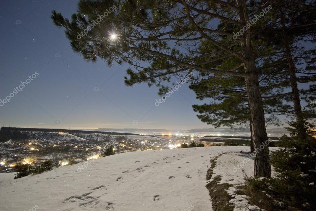 moon shining on a snowy hills with luminous city
