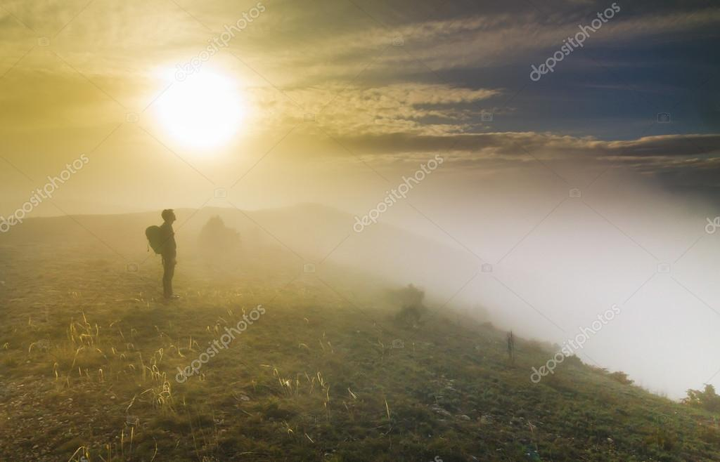 man standing on a hill in foggy weather at sunset