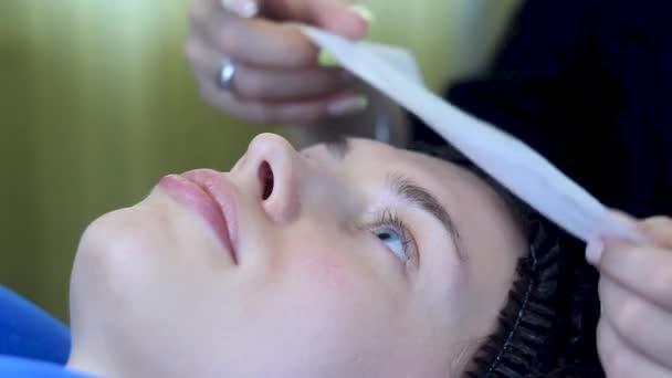 Junge Frau mit Einmalmütze liegt auf Bett, Kosmetikerin legt Serviette
