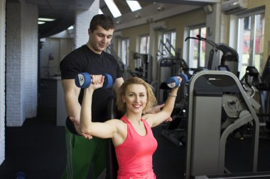 Fitness couple working out with dumbbells in gym