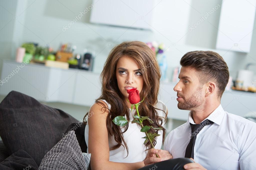 Portrait of two young people holding a rose