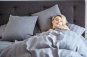 žena odpočívá v posteli s rukama vedle její hlavy