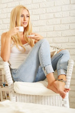 Beautiful elegant woman barefoot drinking coffee