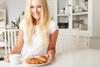 Beautiful young blonde woman enjoying a fresh crispy croissant