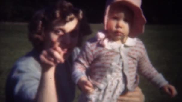 Mother waving baby arm