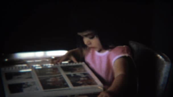 Mädchen schaut auf Familienfotos Album Sammelalbum