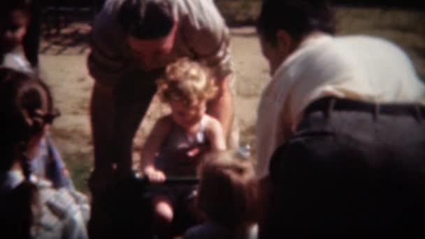 Děti hrají na houpačce s pomocí rodičů, otec