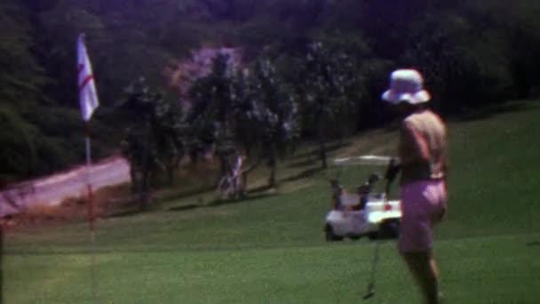 Žena golfista chůzi na poli
