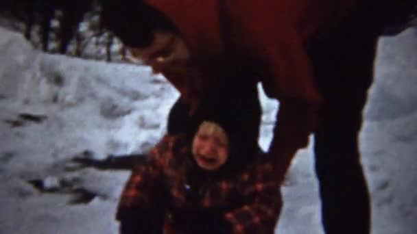 boy falls in snow and mom picks up and brushes off
